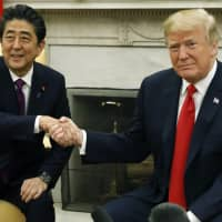 U.S. President Donald Trump shakes hands with Prime Minister Shinzo Abe during a meeting in the Oval Office at the White House in Washington last June. | BLOOMBERG