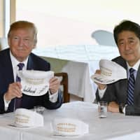 """U.S. President Donald Trump and Prime Minister Shinzo Abe pose for photographs with autographed hats reading """"Donald and Shinzo, Make Alliance Even Greater"""" at Kasumigaseki Country Club in Kawagoe, Saitama Prefecture in November 2017."""