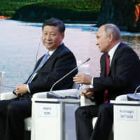 Russian President Vladimir Putin speaks as Prime Minister Shinzo Abe and Chinese President Xi Jinping look on during day two of the Eastern Economic Forum in Vladivostok, Russia, on Sept. 12 last year.   BLOOMBERG