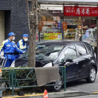 Police officers inspect a car driven by a 79-year-old man that drove onto a sidewalk near Tokyo's Shinjuku Station last month. | KYODO