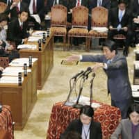 Prime Minister Shinzo Abe (right) gestures during a Lower House session, answering questions from an opposition lawmaker over use of erroneous wage data in a monthly government survey. | KYODO