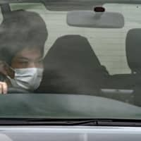 Yukinobu Tomita (seated at rear, wearing a hood) is taken to a police station in Hiroshima Prefecture on Wednesday after being arrested in Otsu, Shiga Prefecture, over a murder-robbery. | KYODO