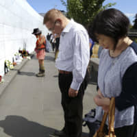 Kazuo and Seiko Horita stand before the name of their daughter Megumi, who died in the 2011 Christchurch earthquake in New Zealand, at a memorial wall in the city on Friday, the eighth anniversary of the disaster.   KYODO