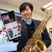 Kanji Toyama, a Nagoya University graduate student and saxophone player, shows off Sonoligo, a website he devised to offer customized information on musicians, venues and concert schedules. | CHUNICHI SHIMBUN