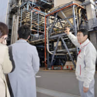 Yasuhiro Sugishita of J-Power, also known as Electric Power Development Co., explains how its coal-fired Isogo power plant in Yokohama works on Dec. 27. | KYODO