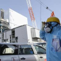 A worker passes by the unit 2 reactor at the Fukushima No. 1 nuclear power plant last week, ahead of a planned check on melted fuel at the reactor on Wednesday. | KYODO