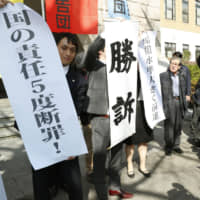 Lawyers representing plaintiffs hold up banners in front of the Yokohama District Court on Wednesday proclaiming that they won their lawsuit. | KYODO