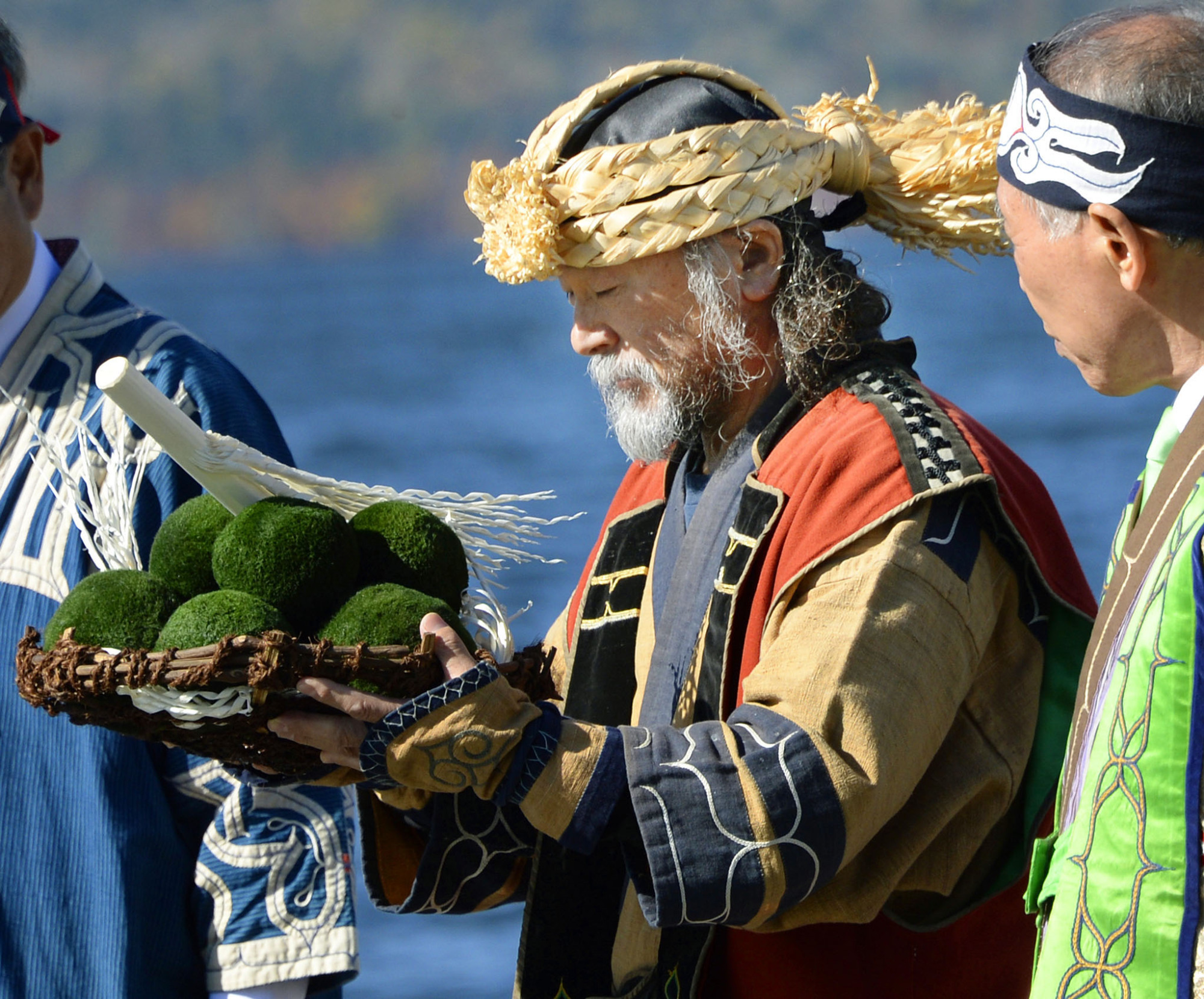 A man offers prayers during an Ainu ceremony to give thanks to nature at Lake Akan in Hokkaido in October 2015. The ceremony involves carefully returning marimo (rare algae balls from the lake's bottom) back to the lake, one by one. | KYODO