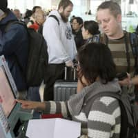 Passengers check in for international flights at Haneda airport in Tokyo. | KYODO