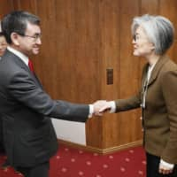 Foreign Minister Taro Kono (left) and his South Korean counterpart, Kang Kyung-wha, shake hands before talks in Davos, Switzerland, on Jan. 23. | KYODO