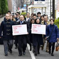 LGBT couples and lawyers demanding marriage equality head to the Tokyo District Court to file lawsuits against the government on Thursday. | KYODO