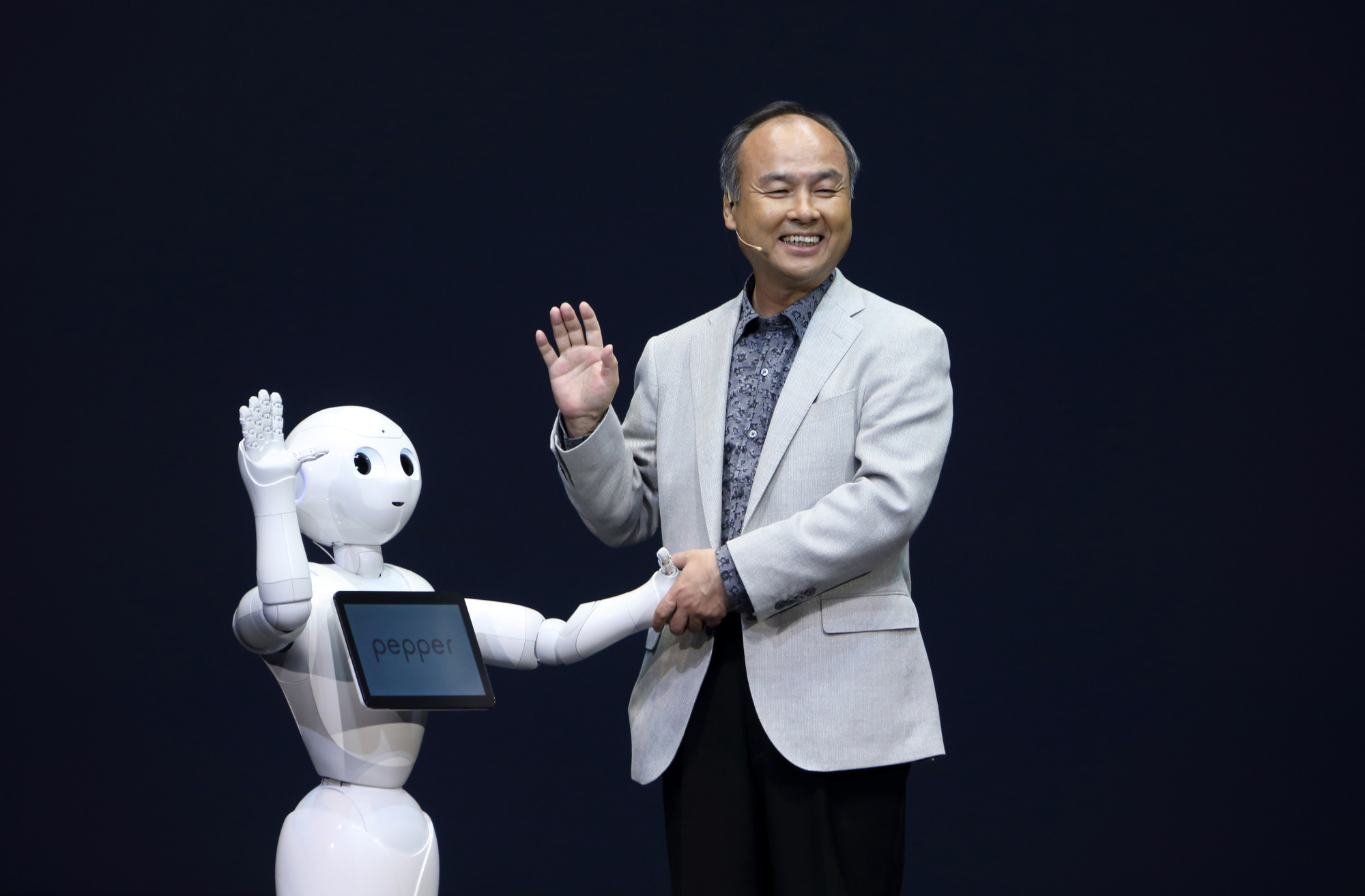 SoftBank Corp. Chairman Masayoshi Son greets the company's Pepper robot during a news conference in Urayasu, Chiba Prefecture, in June 2014. | BLOOMBERG