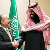 SoftBank Corp. Chairman Masayoshi Son shakes hands with Saudi Arabian Crown Prince Mohammed bin Salman after signing an agreement in New York last March. | BLOOMBERG