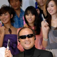 SoftBank Corp. chief Masayoshi Son poses with a product utilizing specially adapted Oakley sunglasses for audio portability during a promotional event in Tokyo in January 2007. | BLOOMBERG