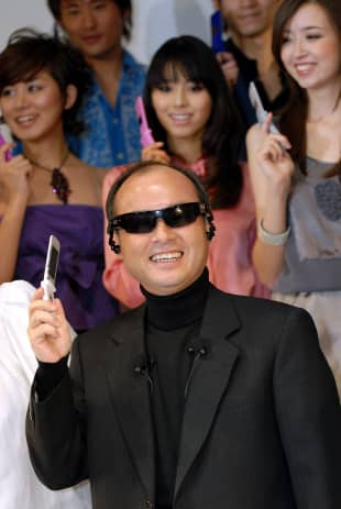 SoftBank Corp. chief Masayoshi Son poses with a product utilizing specially adapted Oakley sunglasses for audio portability during a promotional event in Tokyo in January 2007.