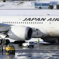 A Japan Airlines Co. plane is seen with its left main landing gear off the runway Friday morning at Narita Airport. The airport briefly closed one of its two runways due to the incident. | KYODO