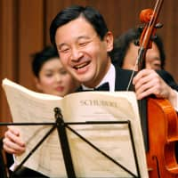 Crown Prince Naruhito laughs as he prepares to play the viola during a photo session before a friendship concert with famous Asian artists in Tokyo in January 2007. | AP