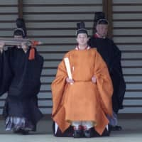 Crown Prince Naruhito walks the corridor after attending a ceremony to celebrate his installation at the Imperial Palace in Tokyo in February 1991. | KYODO
