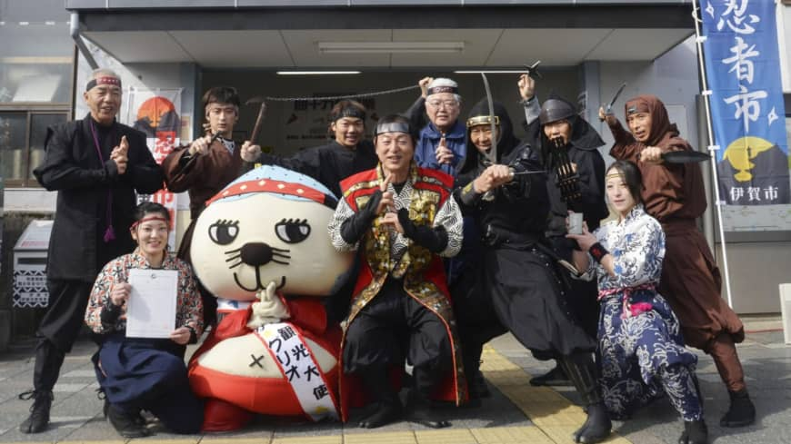 "Sakae Okamoto (center), mayor of Iga, Mie Prefecture, poses as a ninja with others on Friday, locally designated as ""Ninja Day,"" in front of a train station nicknamed ""Ninja City Station."""