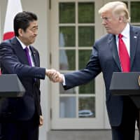 Prime Minister Shinzo Abe shakes hands with U.S. President Donald Trump during a news conference in the Rose Garden at the White House last June. | BLOOMBERG