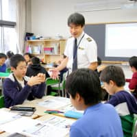 An All Nippon Airways captain talks to elementary school students in Tokyo in October 2017, in an effort to boost the pool of future pilots ahead of an expected shortage. | KYODO