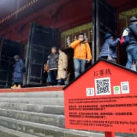 Despite convenience of QR code donations, most worshippers still prefer to offer cash at temples and shrines