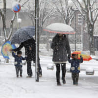 People walk on a snow-covered street in Narita, Chiba Prefecture, on Saturday morning after many areas in the Kanto region, including central Tokyo, saw the season's first snowfall.   KYODO