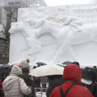 Visitors view a snow sculpture of thoroughbred horses at the annual Sapporo Snow Festival in Hokkaido on Feb. 4. | KYODO