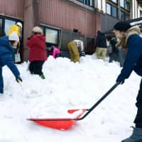 Young people shovel snow in Nishiaizu, Fukushima Prefecture, earlier this month.   KYODO