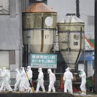 Workers in hazmat suits are seen Wednesday in front of a pig farm in Toyota, Aichi Prefecture, after a swine fever outbreak was detected, leading to about 6,600 pigs being culled. | KYODO