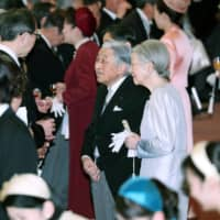 Emperor Akihito and Empress Michiko speak with guests at a tea party they hosted at the Imperial Palace in Tokyo on Tuesday to mark the Emperor's 30-year reign. | POOL / VIA KYODO