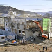The demolition of the former town office building in Otsuchi, Iwate Prefecture, which began on Jan. 19 (above), ended on Wednesday. The town's mayor and 27 other staff members were killed in the tsunami triggered by the devastating earthquake in March 2011. | KYODO