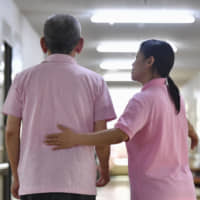A caregiver from Indonesia attends to a resident at a nursing care facility in Tenri, Nara Prefecture, in May 2017.   KYODO