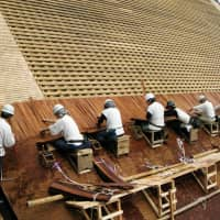 A handout photo shows craftsmen placing Japanese cypress bark shingles on a roof, an example of traditional Japanese architectural techniques that the government is planning to nominate for addition to UNESCO's Intangible Cultural Heritage list. | KYODO