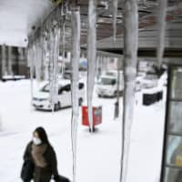 Icicles are seen hanging from a roof Friday in Sapporo, where the temperature dropped to minus 12.5 degrees Celsius before 8 a.m. as the region was hit by the strongest cold front since data compilation began in 1957. | KYODO