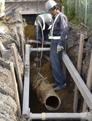 Workers replace an old rusty water pipe in the city of Fuchu, western Tokyo, on Nov. 26.