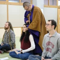 Guests experience Zen meditation at a hostel that used to be the Chonan West Elementary School in Chonan, Chiba Prefecture. D2C X Inc., an operator of a Japan travel information website, promotes tourism in remote areas in Japan, among other tourist spots.