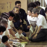 Emperor Akihito and Empress Michiko kneel as they listen to evacuees at a school in Shimabara, Nagasaki Prefecture, after Mount Unzen erupted and killed 43 people in June 1991. | KYODO