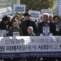 Wartime laborer Lee Chun-sik (center) arrives at the Supreme Court in Seoul, South Korea, on Oct. 30. That day the court ruled that under illegal colonial rule, people who were mobilized by Japanese companies have the right to seek compensation. | AP