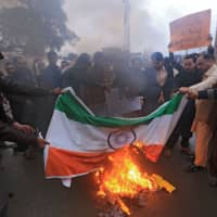 Pakistanis burn an Indian flag  in Peshawar on Tuesday. The protest followed an Indian Air Force strike that day on a militant camp in Pakistan that was carried out in retaliation for a suicide bombing launched by Pakistani militants that killed 46 Indian troops on Feb. 14. | AFP-JIJI