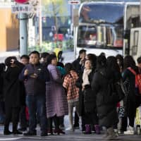 Chinese tourists wait near a tour bus in the Ginza district in Tokyo. As countries from Palau to South Korea have learned the hard way, the Chinese government isn't afraid to divert its tourists and their thick pocketbooks whenever it wants to make a political point. | BLOOMBERG