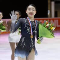 Challenge Cup champion Rika Kihira (front) leads second-place finisher Starr Andrews (center) and Wakaba Higuchi, who placed third, around the rink following the competition on Sunday in The Hague, Netherlands. | KYODO
