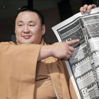 Sekiwake Tamawashi, who won the New Year Basho in January, points to the banzuke for the Spring Grand Sumo Tournament on Monday morning in Osaka. | KYODO