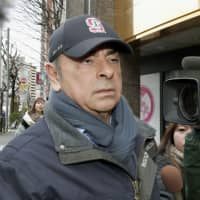 Former Nissan Motor Co. Chairman Carlos Ghosn leaves a condominium in Tokyo on Monday. | KYODO