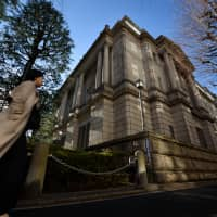 A pedestrian walks past the Bank of Japan headquarters in Tokyo on Monday. | BLOOMBERG