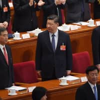 Chinese President Xi Jinping stands with Premier Li Keqiang (right) and Politburo Standing Committee member Wang Yang at the opening session of the National People's Congress in Beijing on Tuesday. | AFP-JIJI