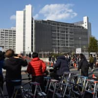News crews wait for former Nissan Motor Co. chief Carlos Ghosn's release outside the Tokyo Detention House on Tuesday. | SATOKO KAWASAKI