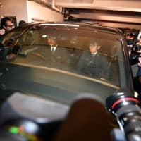 A car carrying former Nissan Chairman Carlos Ghosn (unseen) leaves his lawyers' office Wednesday after he was released from the Tokyo Detention House on bail earlier in the day.   AFP-JIJI