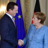 German Chancellor Angela Merkel meets with U.S. Ambassador to Germany Richard Grenell during a reception of the diplomatic corps at the German governmental guest house in Meseberg, northeastern Germany, last July. Merkel on Tuesday insisted Germany will not cut foreign aid to raise military spending, rejecting U..S criticism of its defense outlays. Grenell, who has criticised Germany on issues from its Iran policy to plans to use telecom equipment by China's Huawei, was quick to comment on the projection. | AFP-JIJI