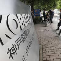 People walk into Kobe Steel Ltd.'s Tokyo headquarters. The steelmaker was ordered by a court Wednesday to pay a ¥100 million fine for fabricating product quality data at its domestic plants. | KYODO